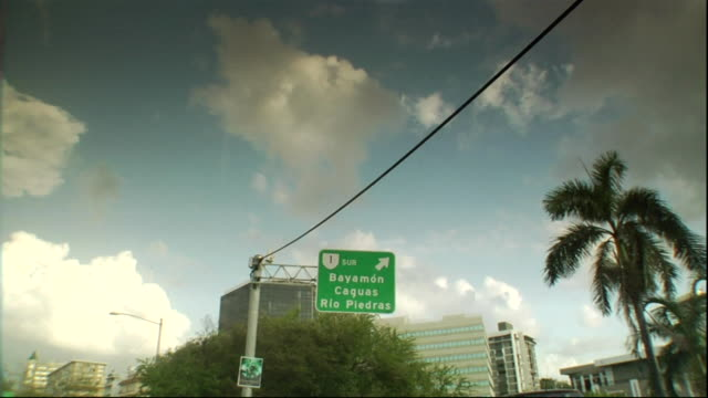 Passing under highway sign Bayamon Caguas Rio Piedras driving along highway road other cars hotel buildings BG