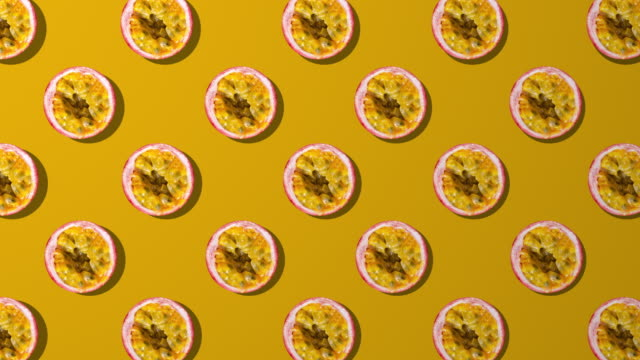 passion fruit slice spinning pattern on orange background - fruit stock videos & royalty-free footage