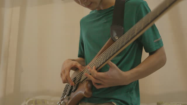 passion with music, close up of young asian boy practicing bass guitar alone in living room - stock video - bass guitar stock videos & royalty-free footage