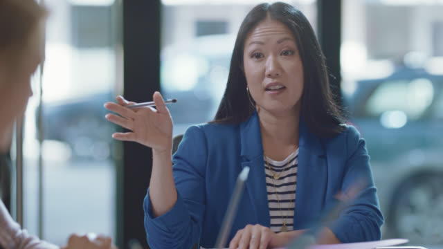 passionate businesswoman takes lead during a team business meeting as she speaks to her fellow colleagues - investment stock videos & royalty-free footage