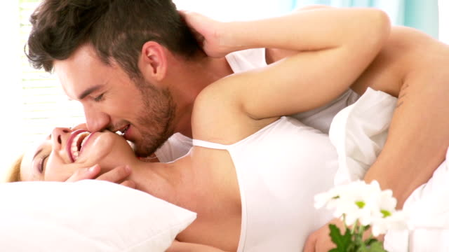 passionate man and woman in bed - flirting stock videos & royalty-free footage