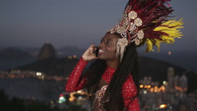 MS A passista carnival dancer uses a mobile phone with Rio skyline in background / Rio de Janeiro, Brazil