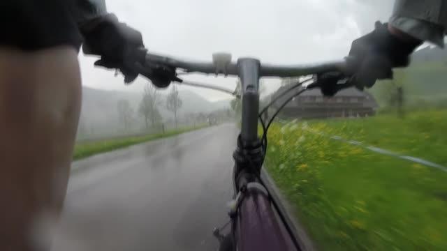 POV past bike handlebars to bicycle piloting mountain road