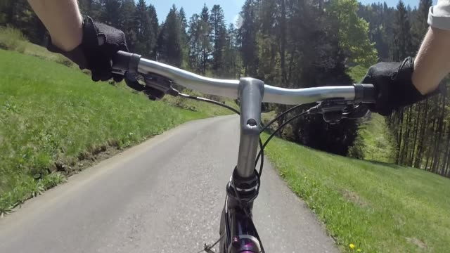 pov past bike handlebars to bicycle piloting mountain road - protective glove stock videos and b-roll footage