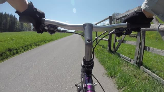 pov past bike handlebars to bicycle piloting mountain road - sports glove stock videos & royalty-free footage