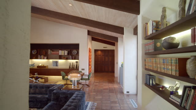 vídeos de stock, filmes e b-roll de ds past book shelves into large living room with original 1971 furnishings and cathedral ceiling - sala de estar