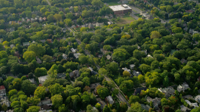 medium aerial past evanston hospital, over tree-covered upscale neighborhood to baha'i house of worship - chicago illinois bildbanksvideor och videomaterial från bakom kulisserna