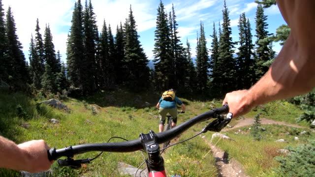 vídeos y material grabado en eventos de stock de pov pasado manillar a ciclista de montaña por delante - manillar