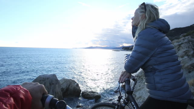 POV past handlebars to woman on bicycle at cliff edge, looking out to sea