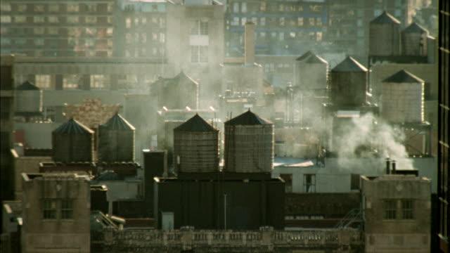 vidéos et rushes de ms pan past high rise to water tanks on rooftop/ new york city - groupe moyen d'objets