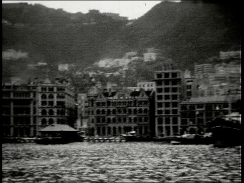 pan past large office buildings in harbor including standard oil co and vacuum oil company / hong kong - 1930年点の映像素材/bロール