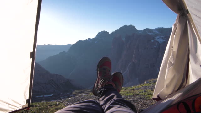 pov past mountaineers feet waking up in tent at sunrise. - tent stock videos & royalty-free footage