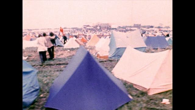 vídeos de stock e filmes b-roll de ts past muddy field full of tents at festival; 1972 - grupo de objetos