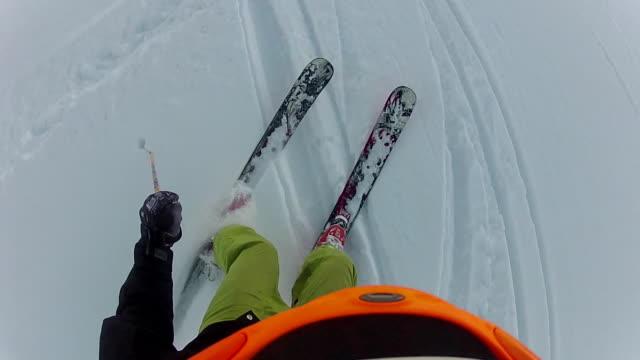 POV past skier's goggles descending through powder snow