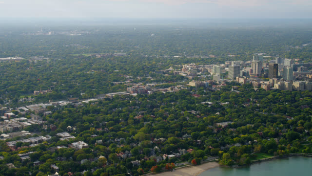 vídeos de stock, filmes e b-roll de wide aerial past tree-covered area to downtown evanston and northwestern university campus along lake michigan - illinois