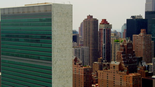 CLOSE UP AERIAL SIDE POV past United Nations Building and surrounding apartment buildings