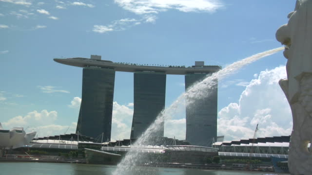 zi past water from fountain to modern skyscraper (marina bay sands) in fullerton area of clarke quay area / singapore - merlion fictional character stock videos and b-roll footage