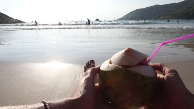 pov past woman's arms holding coconut - human limb stock videos & royalty-free footage