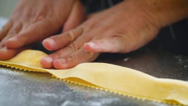 vidéos et rushes de pasta dough is folded over filling and cut - frais