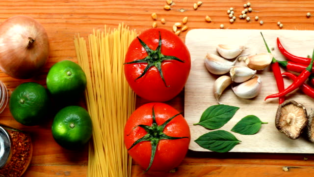 pasta ingredients on wooden table in kitchen, spaghetti,tomato,garlic,mushroom,line,lemon, chilli, pepper