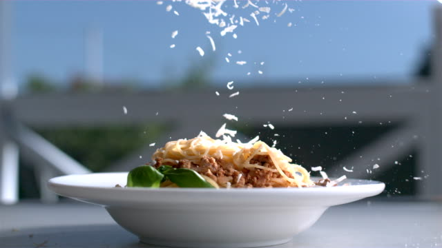 pasta with cheese plate sitting on a table and parmesan is falling on basil and spaghetti in slow motion - pasta video stock e b–roll