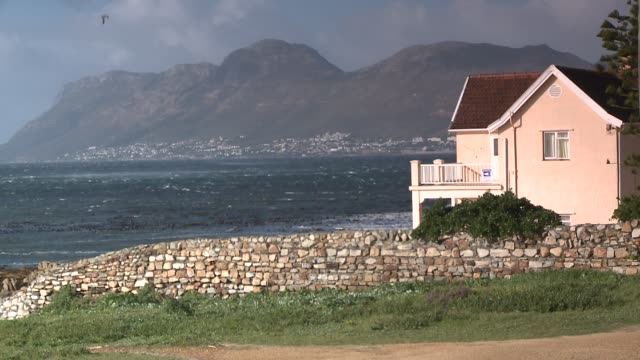 a pastel beach house overlooks a choppy sea in cape town, south africa. available in hd. - beach house stock videos & royalty-free footage