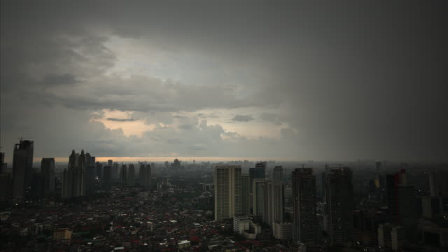 pastel coloured evening clouds drift over the skyscrapers and skyline of jakarta. - natural land state stock videos & royalty-free footage