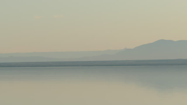 4k pastel light orange and bluish gray lake with mountains in silhouette on the horizon dusk the salton sea - san andreas fault stock videos & royalty-free footage