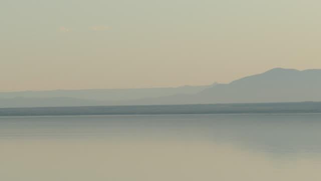 4k pastel light orange and bluish gray lake with mountains in silhouette on the horizon dusk the salton sea - インペリアルバレー点の映像素材/bロール