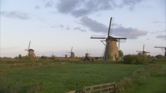 a pastel sky glows above windmills in kinderdijk netherlands. available in hd. - netherlands stock videos & royalty-free footage