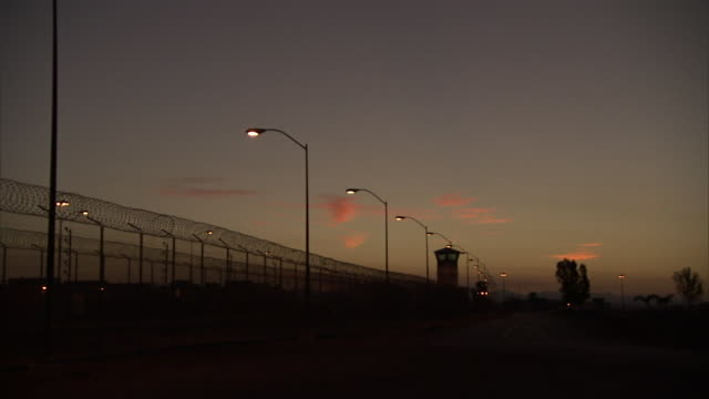 a pastel sky silhouettes prison grounds in california. - prison building stock videos & royalty-free footage