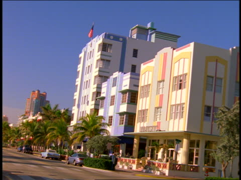 canted pastel-colored buildings along street / south beach / miami, florida - アールデコ点の映像素材/bロール