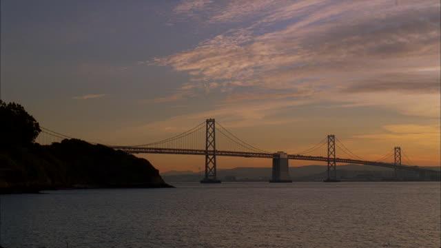 pastels color the sunset sky over san francisco's golden gate bridge. - san francisco bay stock videos & royalty-free footage