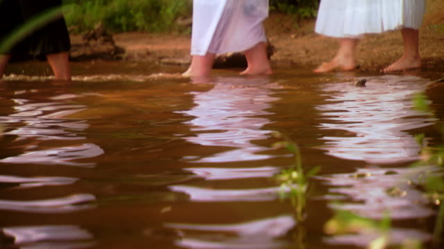 reenactment ws pastor welcomes and leads line of people dressed in white to walk into lake during baptism ceremony   / fairfax station, virginia, united states    - walking in water stock videos & royalty-free footage