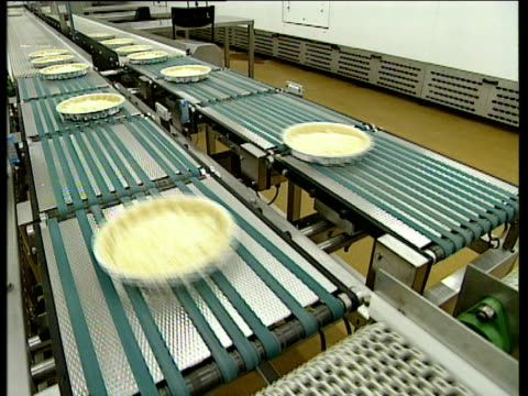 pastry cases on production line filled with egg mixture - baked pastry item stock videos & royalty-free footage