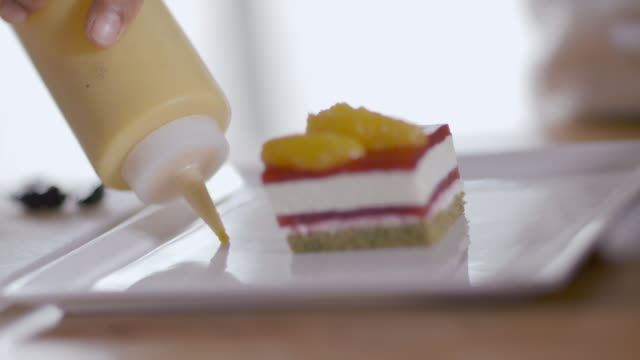 pastry chef decorates dessert dish with yellow sauce from squeeze bottle - カスタードクリーム点の映像素材/bロール