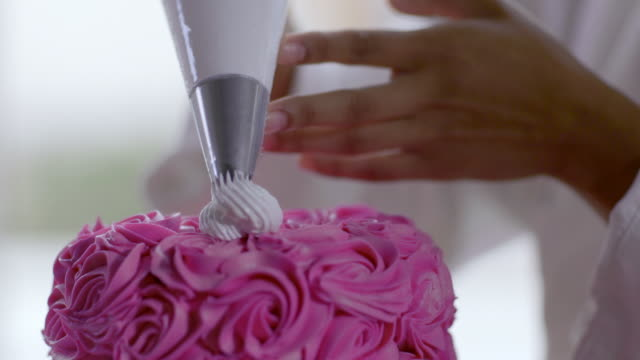 Pastry chef decorates gourmet cake with icing