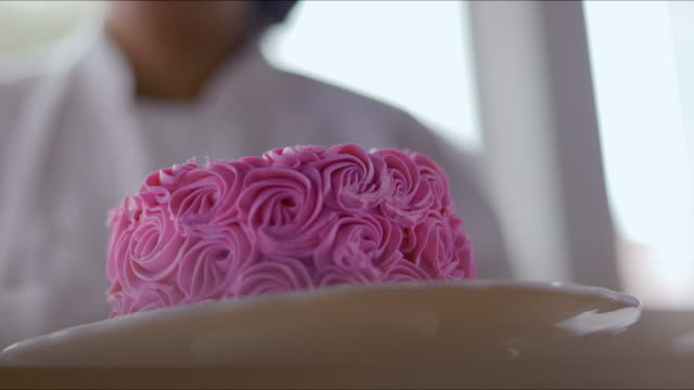 Pastry chef decorates pink cake with white frosting