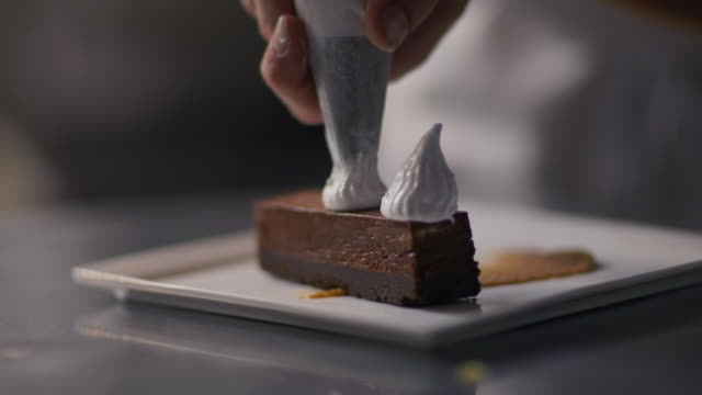 pastry chef decorates s'mores dessert with special marshmallow cream in restaurant kitchen - bakery stock videos and b-roll footage