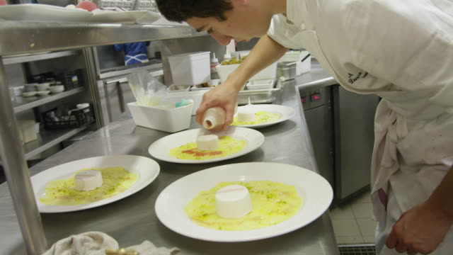 POV LA pastry chef finishing dessert plates in restaurant kitchen cold plating area