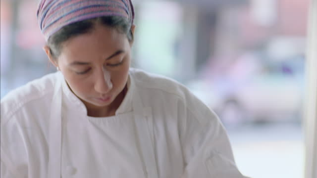 pastry chef flattens dough with rolling pin in restaurant window - brot backen stock-videos und b-roll-filmmaterial