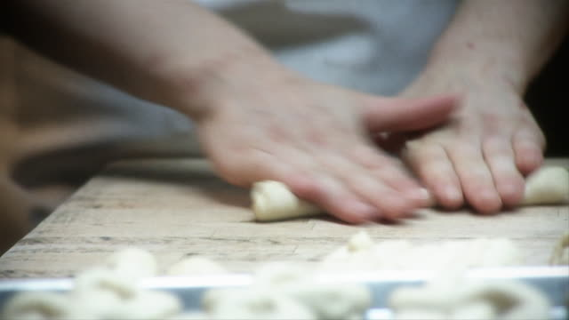 A pastry chef prepares pretzels in a kitchen.