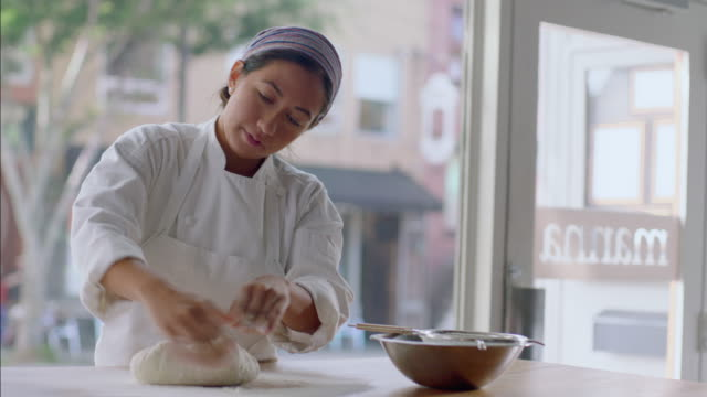 Pastry chef rolls dough in flour and shapes with hands in bakery window