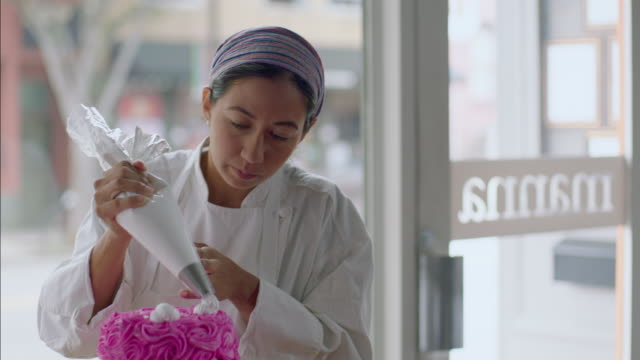 Pastry chef rotates tray and puts icing on cake with decorating bag