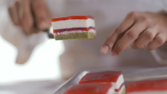 pastry chef's hands  lift cake from tray and place on dessert dish - tart dessert stock videos & royalty-free footage