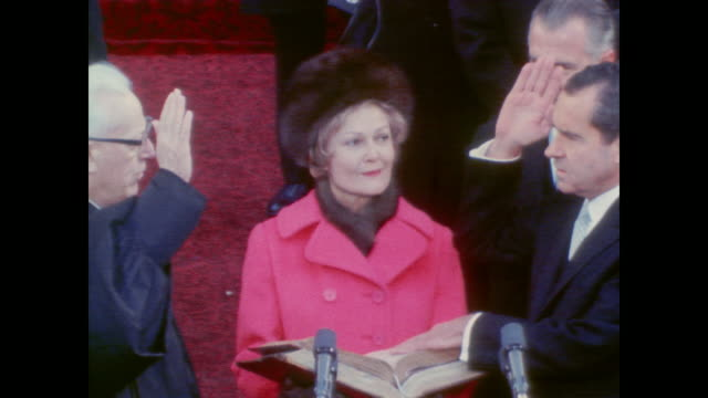 Pat Nixon holds bible as Chief Justice Earl Warren swears Richard Nixon into office