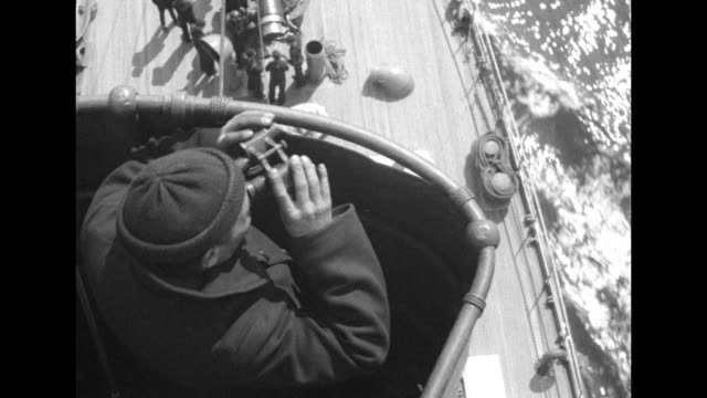 vidéos et rushes de patched canvas sails with a schooner riding ocean swells / a man in a knit cap in the crow's nest peers through binoculars with the deck of the ship... - casquette