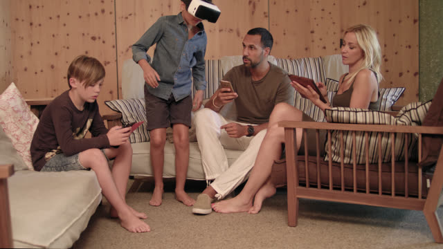 a patchwork family using digital devices in a hotel lounge - vr headset, iphone and a tablet pc and ipad involved - children gaming and being astonished, digital detox far away - detox stock videos & royalty-free footage