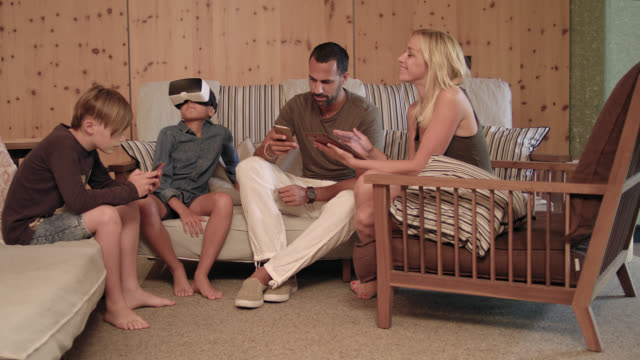 A patchwork family using digital devices in a hotel lounge - VR headset, iphone and a tablet PC and iPad involved - children gaming - togetherness – mother with long blonde hair and father with short dark hair and trimmed beard, kids in trendy clothes.
