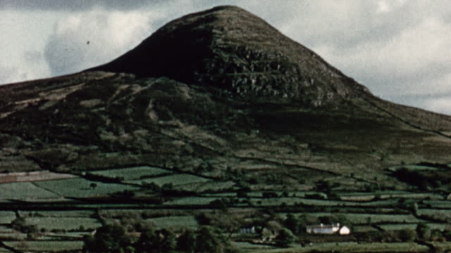 1956 MONTAGE Patchwork farmland of small fields and stone walls, with mountains behind / Northern Ireland, United Kingdom